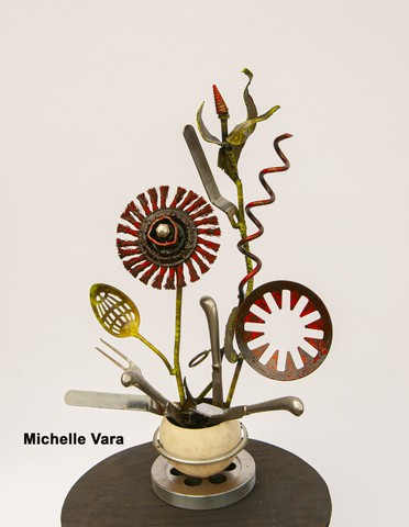 Flower arrangment made with common household objects welded into metal sculpture.